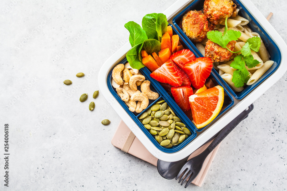 Fototapety, obrazy: Healthy food lunch box. Vegan food: beans meatballs, pasta, vegetables, berries, seeds and nuts in a container
