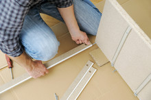 A Man Is Assembling The Furniture At Home.