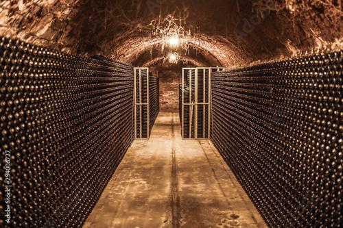 Stampa su Tela  Winebottles in spooky wine cellar
