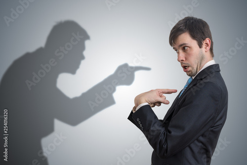 Photo Shadow of man is pointing and blaming businessman