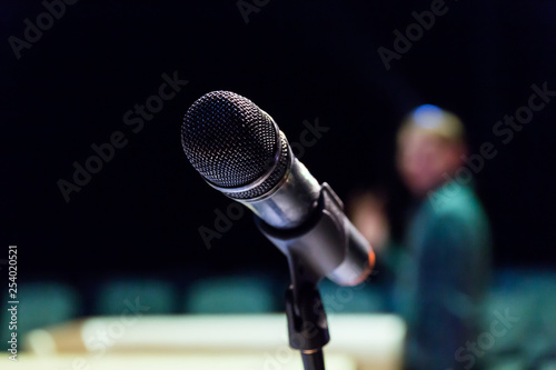 Wireless microphone on stand on blurred background. Unfocused image of people in the background. - 254020521