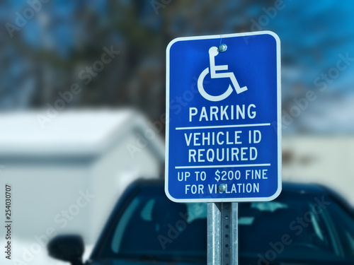 Fotografia, Obraz  Handicapped parking sign with car, building and tree in snow covered parking lot in winter