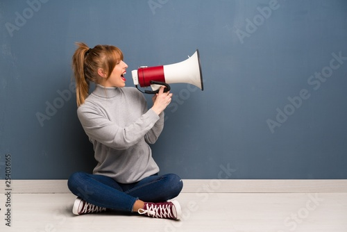Photo Redhead woman siting on the floor shouting through a megaphone