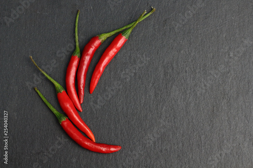 Cadres-photo bureau Hot chili Peppers Group of hot spice red chilli fresh cayenne pepper on a black graphite slate stone surface. Natural vegeterian diet organic vegetable. Dark food foto