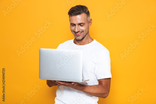 Fotografía  Image of attractive guy 30s in white t-shirt holding and using silver laptop