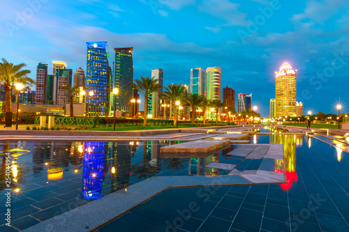 Fényképezés  Doha West Bay high rises at blue hour reflecting in the water of park in Downtown