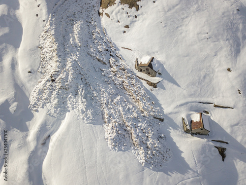 Slika na platnu Aerial view of snow avalanche on mountain slope