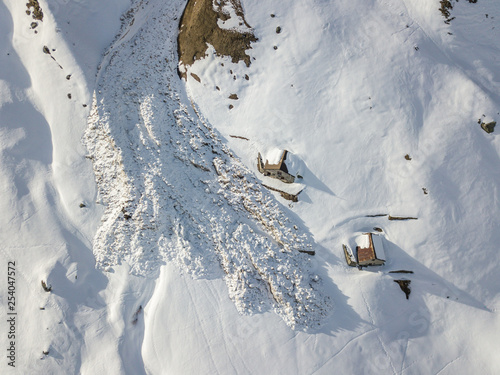 Leinwand Poster Aerial view of snow avalanche on mountain slope