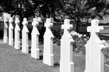 Crosses In Cemetery. White Gravestones Going In Perspective.black And White Image