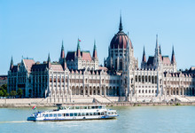 Hungarian Parliament Building In Budapest With White Cruise Tour Boat And Danube River In Foreground - Budapest, Hungary