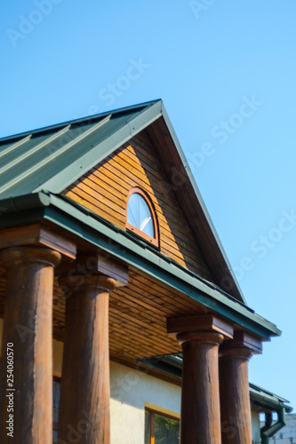 Foto  The Massive Wooden Columns of the Porch Entrance to the House of Thick Solid Logs
