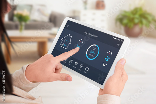Stickers pour porte Pierre, Sable Modern software to home control on tablet display. Woman control temperature in living room. Close-up.