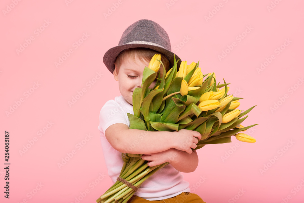 Fototapety, obrazy: Adorable smiling child with spring flower bouquet looking at camera isolated on pink. Little toddler boy in hat holding yellow tulips as gift for mom. Copy space for text