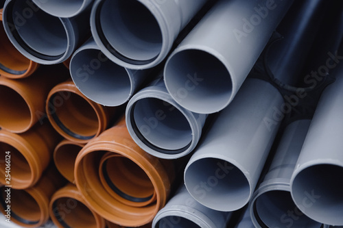 Fototapeta PVC plastic construction pipes for water are displayed in row on counter