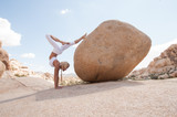 Fototapeta Kamienie - Desert Yoga Boulder Supported Scorpion Woman.  Scorpion Pose (Vrschikasana) is an advanced pose.