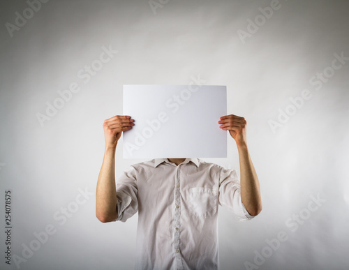 Young man holding white paper in his hands. Wallpaper Mural