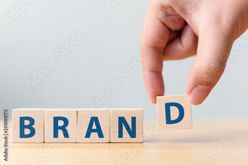 "Obraz Hand of male putting wood cube block with word ""BRAND"" on wooden table. Brand building for success concept - fototapety do salonu"