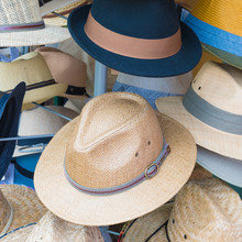Vintage Straw Hats Stacked In Front Of Shop