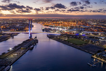 Aerial View Of The Bolte Bridge In Melbourne Australia At Sunset, With The Industrial Port In The Background