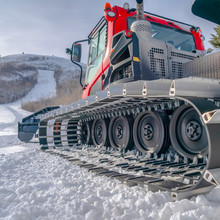 Snow Grooming Machine Against The Snowy Ski Slope
