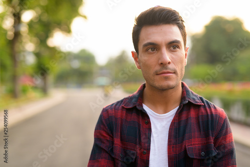 Fotografia  Face of young thoughtful Hispanic hipster man at the park