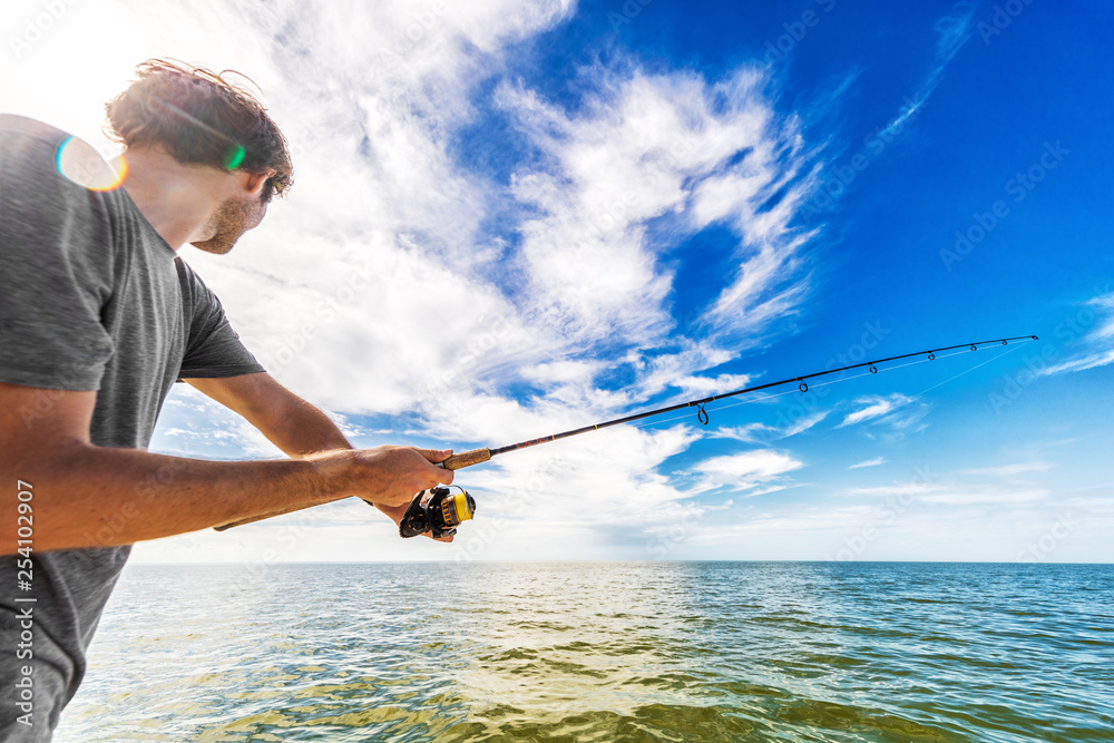 Fototapeta Man fishing in the sea from boat casting bait throwing line.
