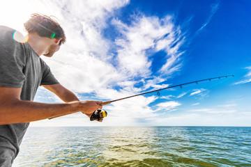 Čovjek koji lovi u moru s broda za bacanje mamaca.