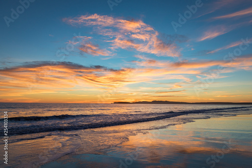 Sunset at Limantour Beach, Pt. Reyes California. Facing northwest with saturated colors and reflections in the water.