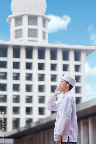 Fotografija Asian man doing azan in the mosque