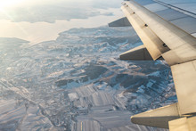 In Winter While The Airplane Is Flying In The Sky Looking Down Through The Windows Seeing Snow Covered Ground, House And Field.