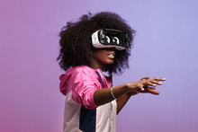 Mod Young Brown-haired Curly Girl Dressed In The Pink Sports Jacket Uses The Virtual Reality Glasses In The Studio On Neon Background