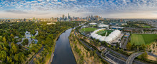 Aerial Panoramic Dawn View Of The MCG And AAMI Stadium, With The CBD In The Background
