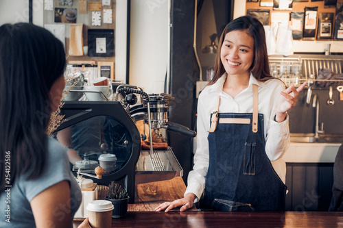 woman barista talking with customer about tasted of coffee cup with