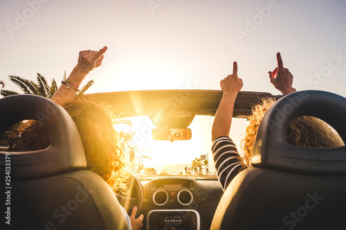 Couple of woman friends traveling and driving having a lot of fun dancing in the car with opened roof and summer vacation sunset ocean in front - concept of friendship together and nice lifestyle - 254133379