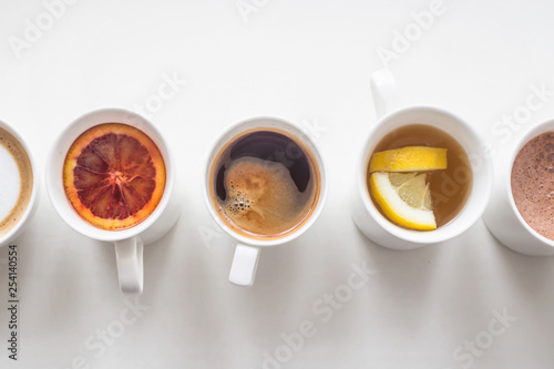 Several different hot drinks on the white table - coffee shop menu