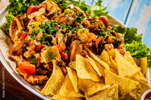 Pinturas sobre lienzo  Grilled chicken meat with nachos and vegetables on wooden background