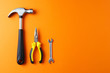 canvas print picture - Metal hammer, pliers, a key on an orange background