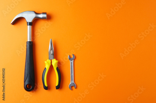 Fotomural  Metal hammer, pliers, a key on an orange background