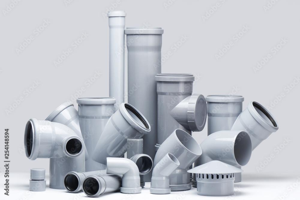 Fototapeta Plumbing, sewage. Gray polypropylene tubes on a white background in futuristic style