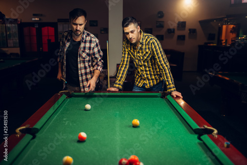 Fotografia Two male billiard players with cue, poolroom
