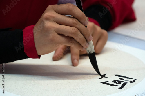 Fotografie, Obraz  japanese woman writing ideograms with brush