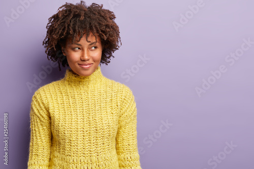 Fotografia  Headshot of curious satisfied dark skinned woman with curly haircut, looks away