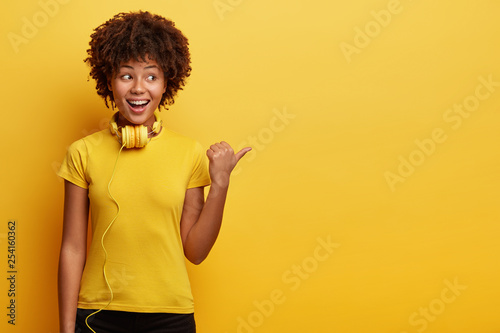 Waist up shot of African American hipster girl being amused by listening music, has modern headphones on neck, points aside, shows way to electronic shop, has cheerful expression, isolated on yellow - 254160362