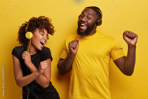 Foto  Cheerful young African American bloggers enjoy favourite playlist in headphones,