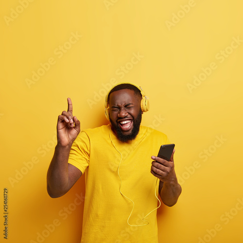 Happy man with dark bristle forgets about all troubles while listens favourite song, likes beats in headphones, connected to modern cellular, points with fore finger upwards, isolated on yellow wall - 254160729