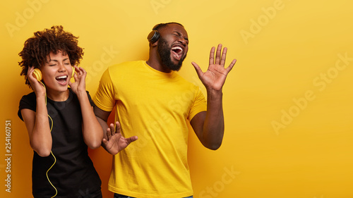 Optimistic black female and male enjoys favourite moment in song, smile from joy and pleasure, dance while listen music in headphones, sing aloud, isolated over yellow wall with free space right - 254160751
