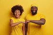canvas print picture - Studio shot of overjoyed satisfied woman and man with dark skin, give fist bump, agree to work together, have success in project work, wear yellow attire, pose in studio. Cooperation concept