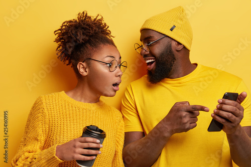Surprised curious dark skinned woman looks at screen of boyfriends cellular, reads online post with interesting content, excited with smartphone or app features, isolated over yellow background Tableau sur Toile