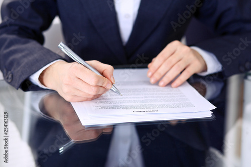 Photo Unknown female hands with pen over document of contract