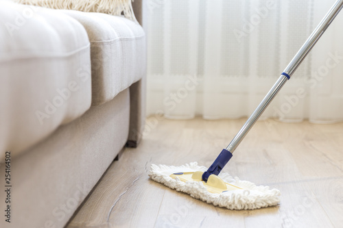 Obraz na płótnie Cleaning floor with white mop near sofa
